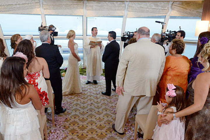 Buddy and Lisa exchange vows while their family looks on.