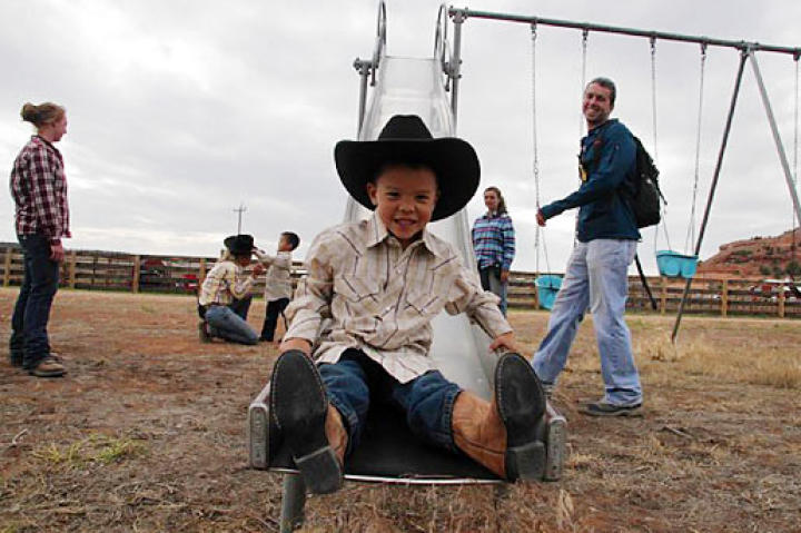 Joel comes down the slide in his cowboy boots at the Dude Ranch.