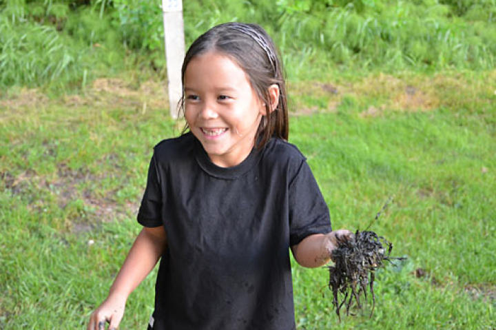 Leah, mid- mud fight, having the time of her life getting her tiny hands messy.