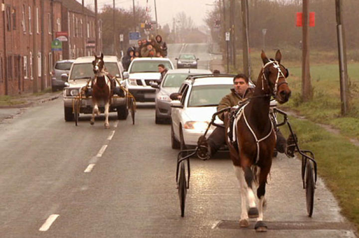 Gypsy men on horses share a highway with cars.