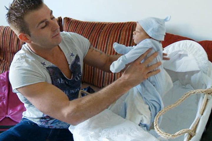 Women are the typical caretakers, but this gypsy tries his hand at swaddling a baby.