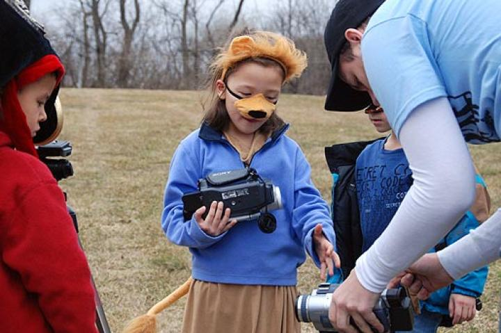 Sam of Movie Makers shows Alexis how to operate a camera.