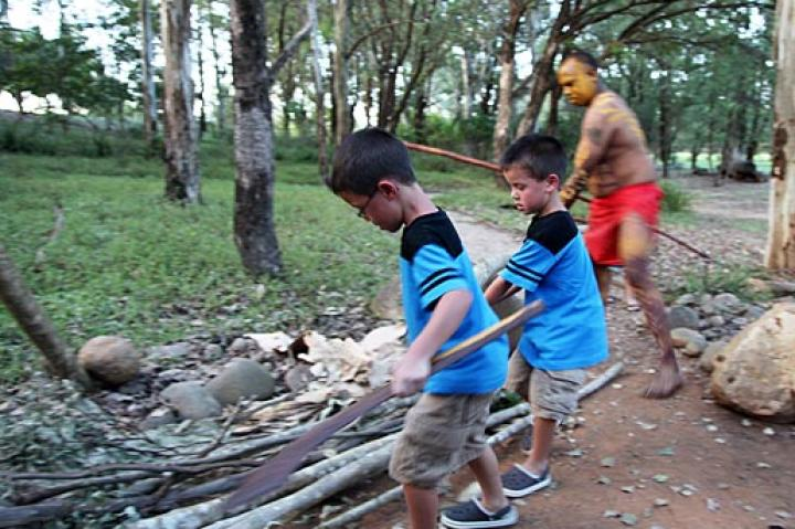 Aaden and Collin help gather wood at Aboriginal Village.