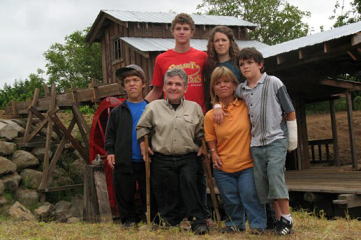 The Roloff Family posing together in front of the farm's saw mill (complete with a 12 foot water wheel).