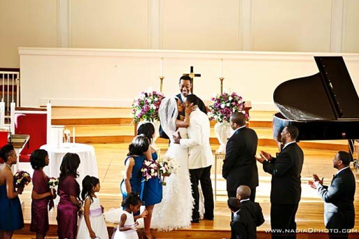 Asha and her groom, Bryson, embrace at the altar.