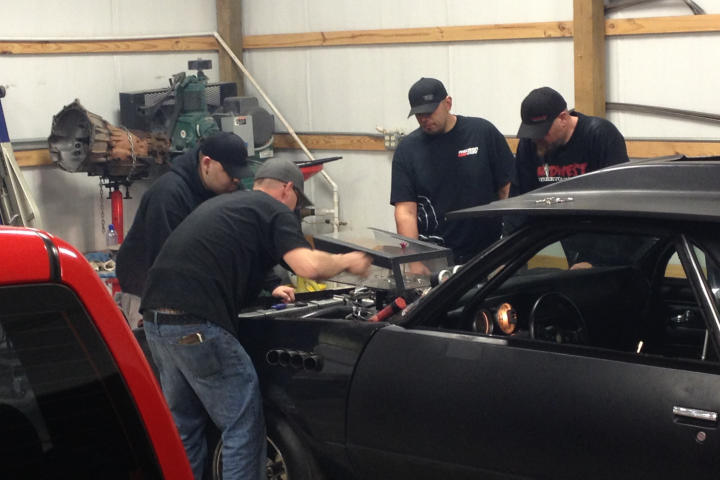 Tyler Priddy (a.k.a Flip), Justin Shearer (a.k.a. Big Chief), Shawn Ellington (a.k.a. Murder Nova) and Danny Parker work on a car together.