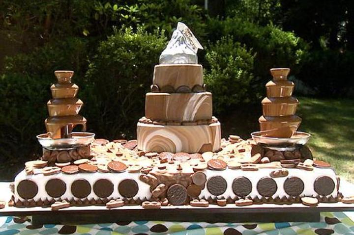 "CHOCOLATE LOVERS CAKE   How was the cake made?  The cake was made of chocolate sponge cake (main cake), chocolate sponge cake (smaller cakes) with the following fillings: peanut butter cup filling, chocolate bar filling, peppermint filling, coconut flake and almond filling, marble chocolate fondant (covered the upper tiers), Hershey Kisses (border on bottom tier), melted Hershey Bars (chocolate fountain and river), Rice Krispies Treats (giant kiss on top of cake), and modeling chocolate (silver wrapper). What's memorable about the cake?  Simeon's wife loves chocolate so he wanted Buddy to create the most ""chocolately thing he could think of"" that included her favorite chocolate bars. This cake was a chocoholic's dream complete with chocolate cake, candy bar fillings, a chocolate fountain and even a chocolate river!  Click ""Next"" to see the next sketch."