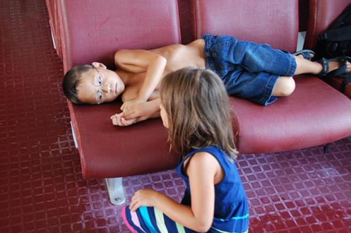 Alexis consoles her seasick brother Aaden on the boat.