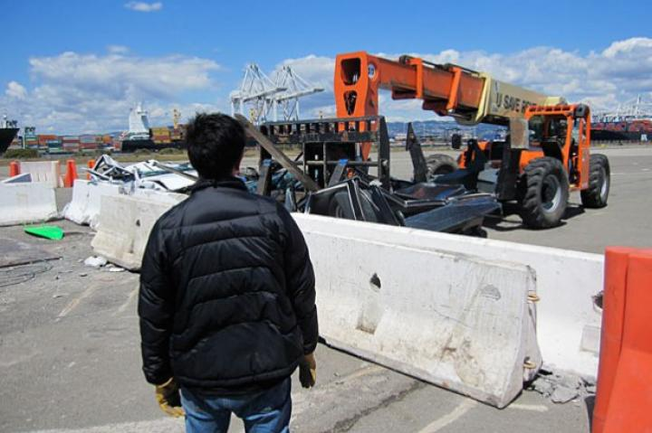 "As Grant Imahara looks on, Tory Belleci uses a crane to hoist one of the ""Surf and Turf"" test cars. Did"