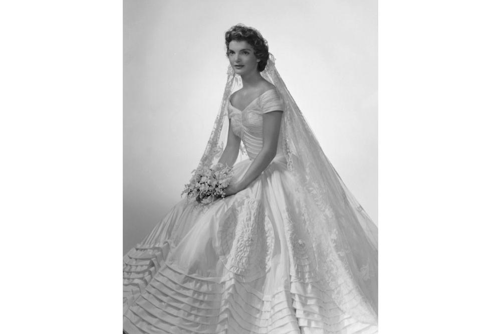 Jackie Kennedy poses for her bridal portrait in her Anne Lowe wedding dress at Bachrach's New York studio in 1953.
