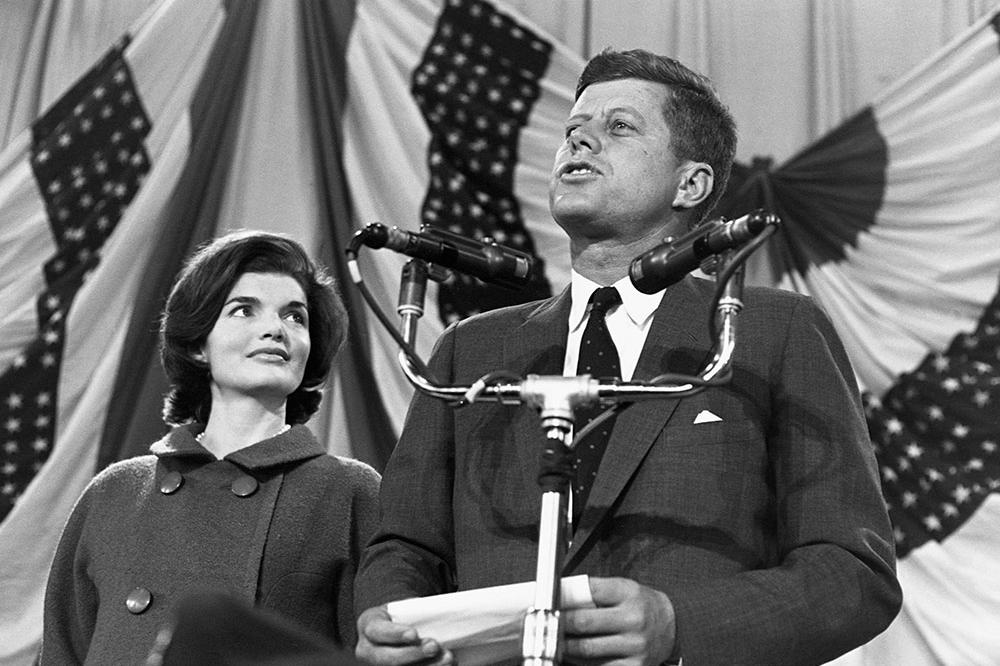 Jackie looks on as her husband delivers a speech.