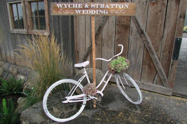 A sign and vintage bike greet the wedding guests.