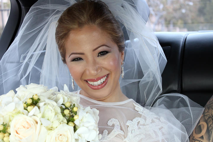 Joi smiles on her wedding day. She's wearing her Something Borrowed dress designed by Kelly Nishimoto.