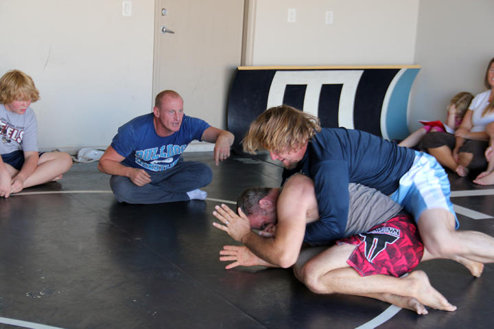Kody and his friend Brett wrestle while their trainer Sean cheers them on.