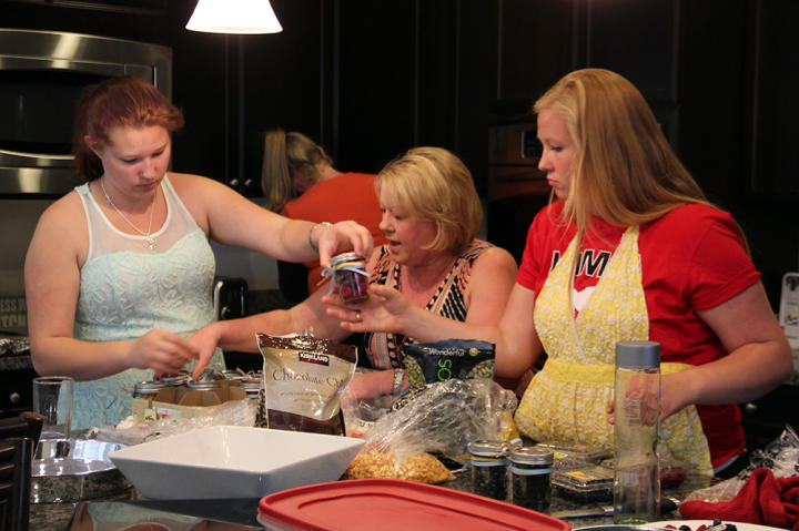 Mykelti, their neighbor Beverly, and Aspyn help prepare party food back at the house.