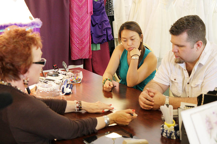 Louis and Aya visit a local bridal salon to find her wedding dress. They discuss their budget with the consultant.