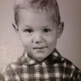 In the first grade, Monte wears a shy smile and a plaid shirt buttoned