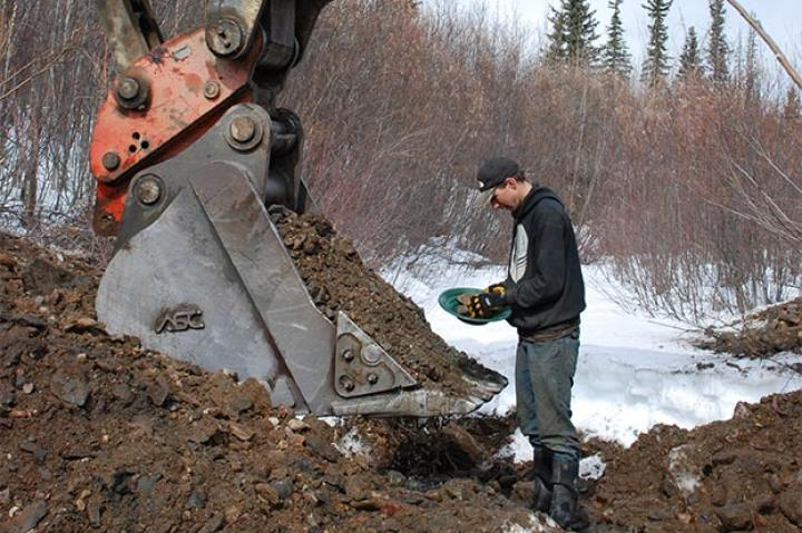 Parker examines a pan of what could be pay dirt.