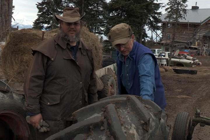 Otto and Shane stands near a tractor and inspect the tires beofre heading out on the cattle drive.