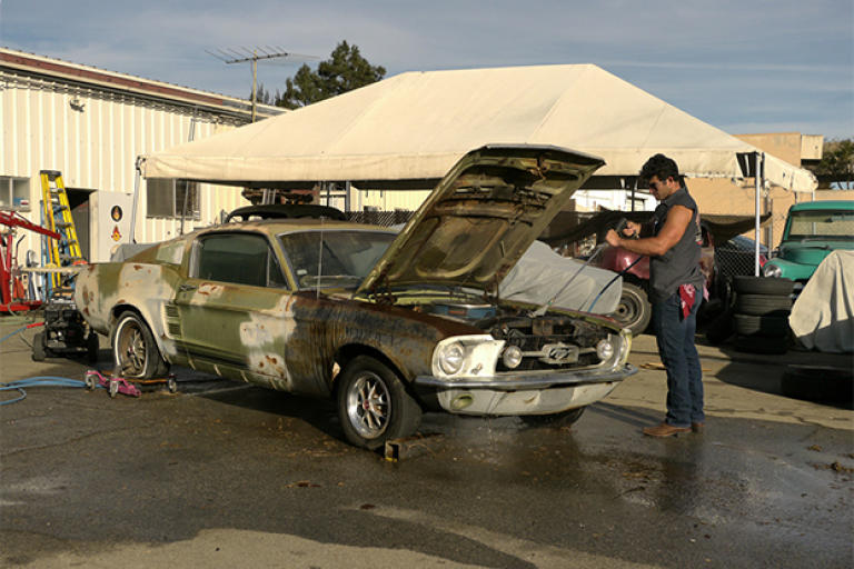 Billy Derian Jr. power washes a 1967 Ford Mustang.