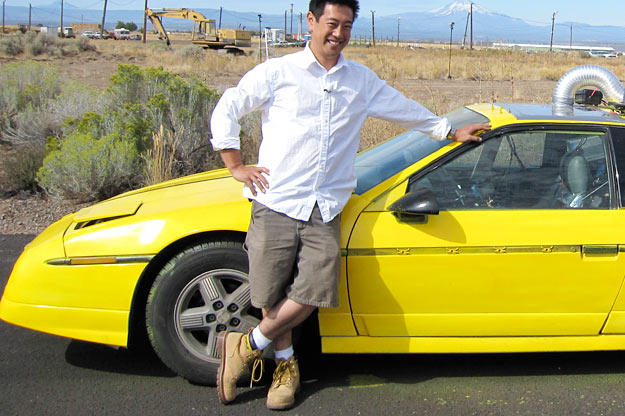 Grant Imahara poses with the remote-controlled car he built to test whether a speeding vehicle can truly skip across a water's surface, as seen in