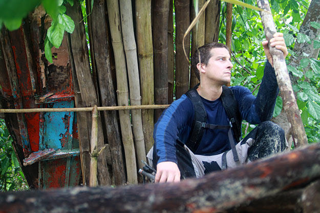 On an island in the Malay Archipelago  Bear Grylls sits by his shelter, which he built from bamboo and bits of a broken-up boat. Not only does it protect him from the elements, but its roof is also capable of collecting rain water for drinking.