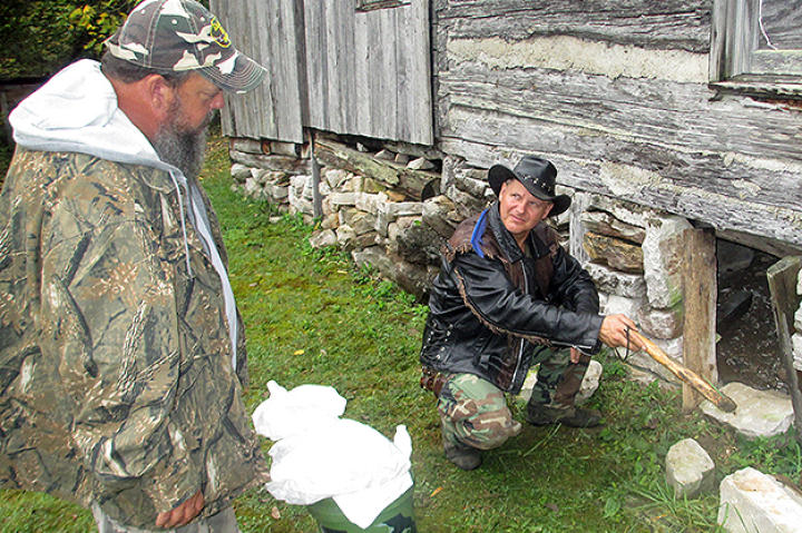 Ernie Brown, Jr., the Turtleman, and Neal James find the critter's entrance to where it dens.