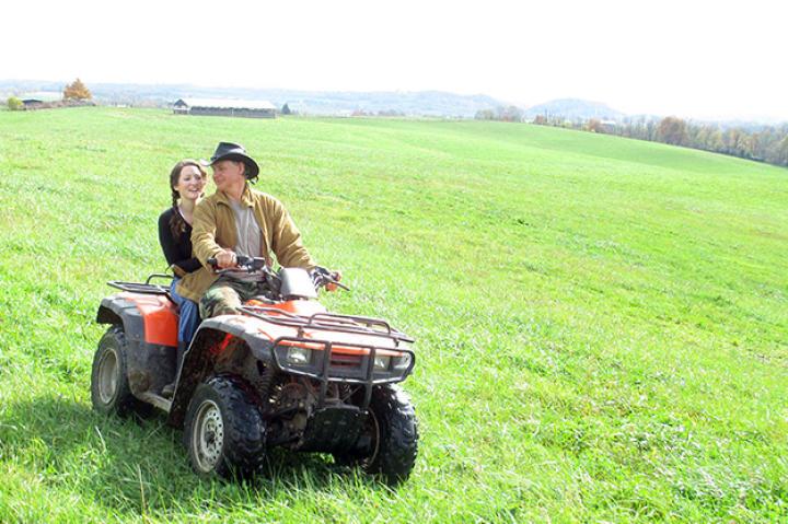 Ernie Brown, Jr., and farmer Cole Henson search the fields for Hugh Heifer.