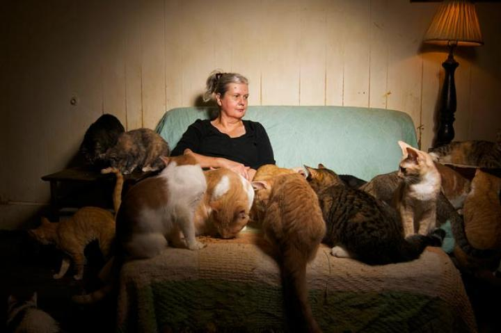Marie sits with her cats.