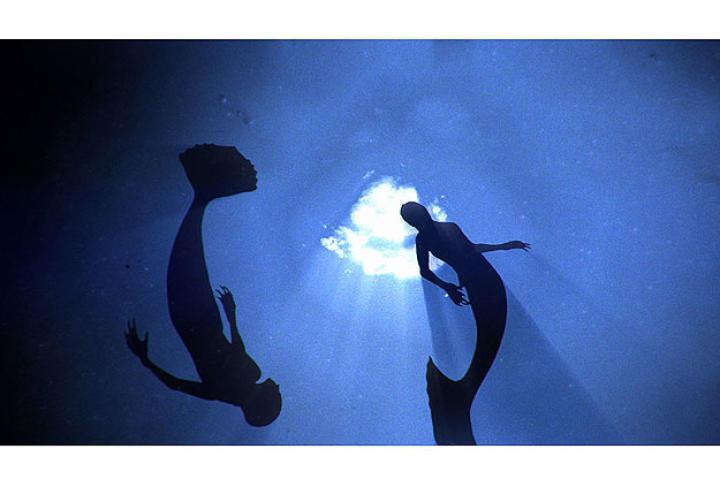 Mermaids swimming through the deep ocean.