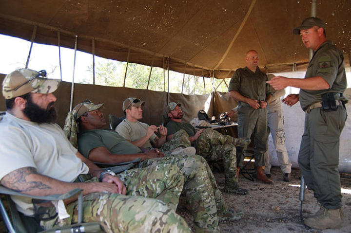 "Oz (medic, Green Beret), Rob (intel, Navy SEAL ret.), Jeff ""Biggs"" (sniper, Navy SEAL fmr.), Craig ""Saw"" (team leader, Navy SEAL fmr.) all seated being briefed by Li Loeriet (standing with cap on head) from Quemic Anti-Poaching Unit about the situation of poaching in South Africa."