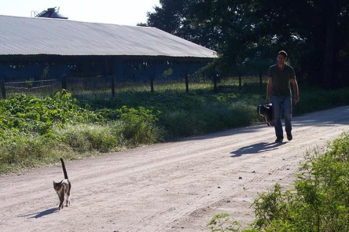 John travels along on dirt path with guitar and cat.