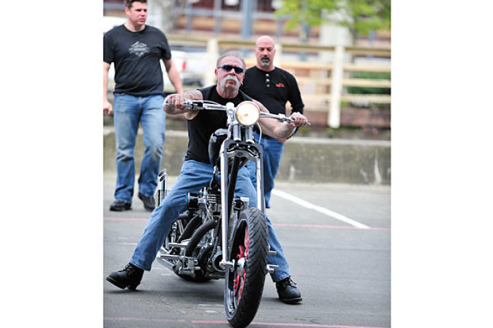 Senior with Jason Pohl and Mike Ammirati looking on rides the Deadliest Catch Bike to its reveal.