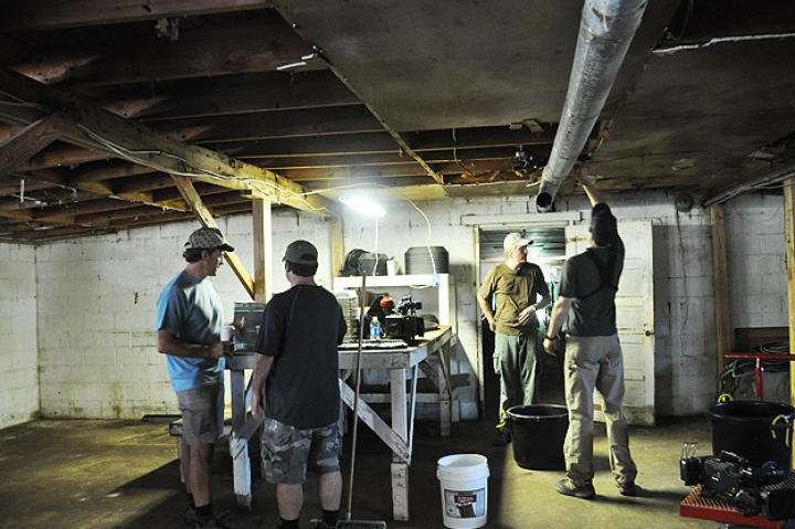 Doug Glover and Troy Paff set up the first interior shot at Ghann's Cricket Farm, while Mike Rowe and Dave Barsky consult.