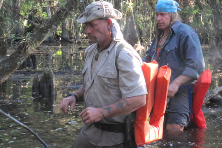 Cody and Dave move cautiously through the dark, danger-laden waters. With his bare feet and legs, Cody admits to being way out of his comfort zone, but Dave once hunted reptiles in these swamps and feels right at home.