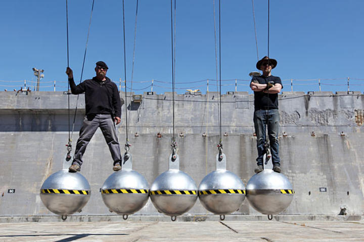 Jamie Hyneman and Adam Savage perch atop giant steel balls. (We'll spare you the jokes.)