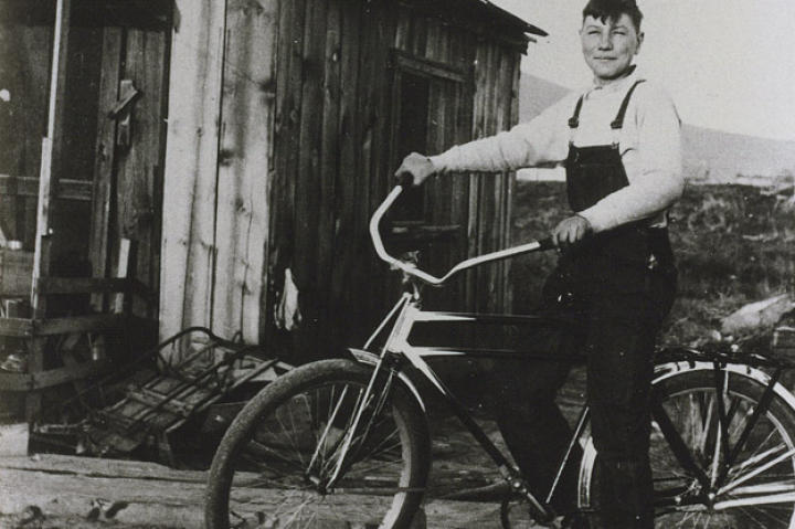 John shows off the bike he bought in 1933 with his earnings from delivering newspapers. John also made money selling used bottles to bootleggers. He collected the bottles in the alleys of Klamath Falls (an early recycler!) and sold them for a penny apiece. Sometimes he could make as much as 15 cents a day!