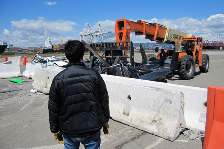"""As Grant Imahara looks on, Tory Belleci uses a crane to hoist one of the """"Surf and Turf"""" test cars. Did"""