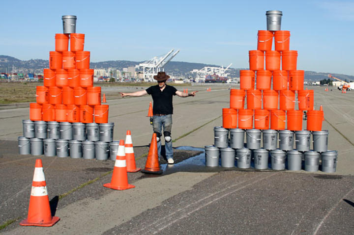 "In the ""Fixing a Flat"" race, Adam Savage thought his manhole-cover tires would out-perform Jamie Hyneman's steel rims. He was wrong. He would soon be crashing the water pyramid on the right like it was invisible."