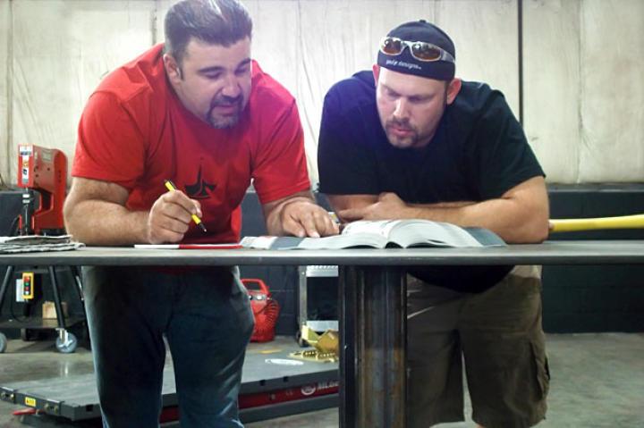 Vinnie DiMartino and Paul Jr. pore over designs.