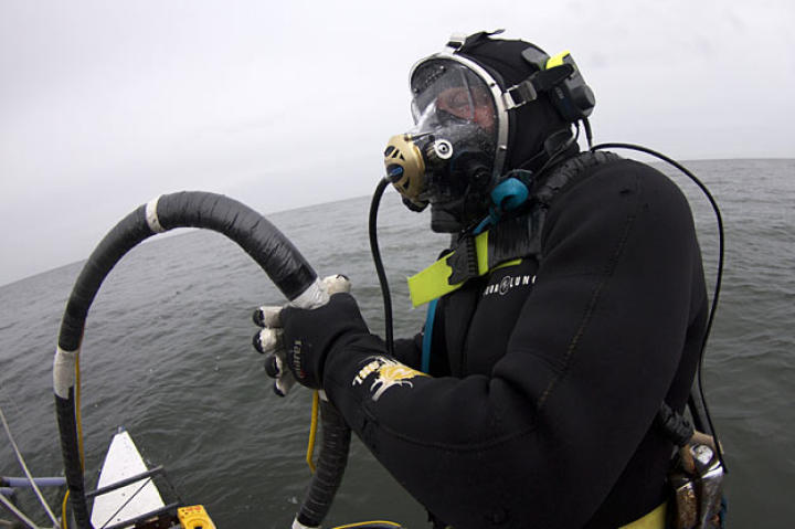 Holding his air hose to keep it clear during the dive, Scott gets ready to enter the water.