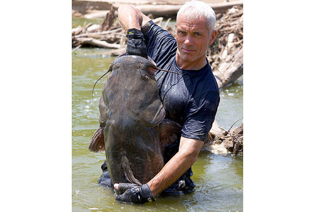 Jeremy Wade holds a flathead catfish he pulled from its underwater lair using only his hands.