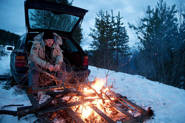 Les Stroud warms by a fire in the Norwegian mountains.