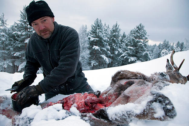 Les Stroud cleans a fresh kill in the snow.