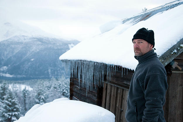 Les Stroud in front of a modest shelter in the extremely cold Norwegian weather.