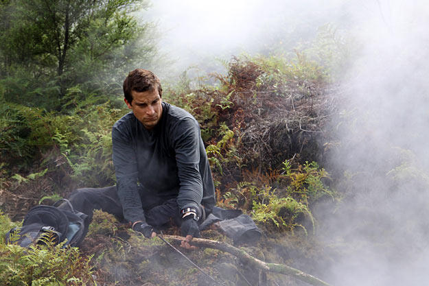 In New Zealand, after using his cell-phone battery to start a fire, Bear Grylls takes a minute to warm up.