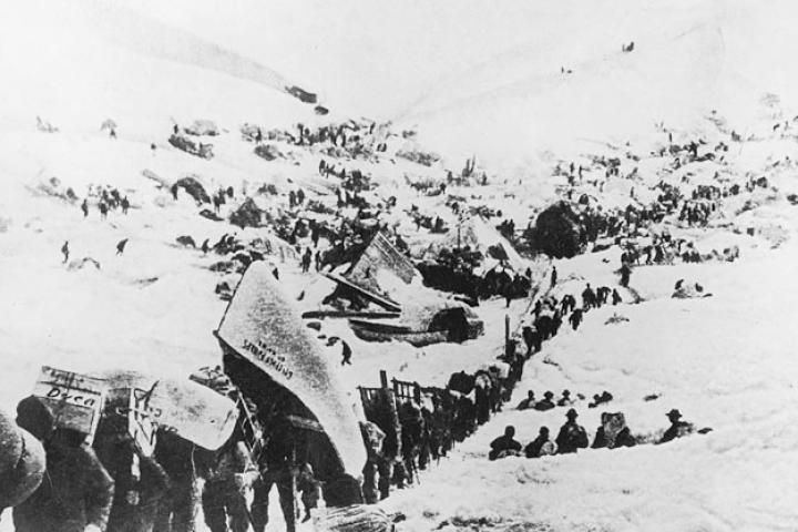 "A line of prospectors begin their ascent toward the Chilkoot Pass that will take them over the border into Canada. Heavy snows in the fall of 1897 did little to stem the tide of fortune-seekers. Most of the arrivals were ill-prepared for what lay ahead as suggested by the fellow carrying a canoe on his back. Another carries a cumbersome crate labeled ""Dyea"" for the Alaskan town where many picked up supplies before heading out.   Few of the thousands who set out had any skill at gold prospecting. Likewise, hardly any carried sufficient supplies so that over the next months the greatest danger facing the Klondike miners was famine."