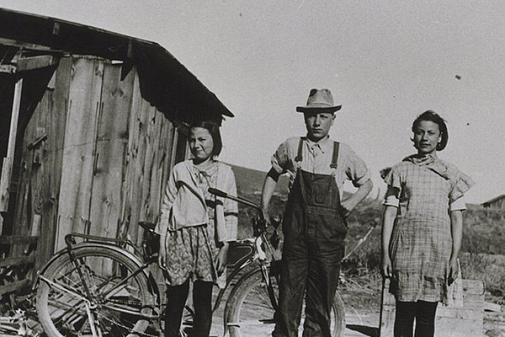 In this 1932 photograph, young John Schnabel and sisters Margaret and Mary stand in front of the shack they grew up in outside of Klamath Falls, Oregon. The 12 by 16 ft building was for the women while John and his brothers stayed in the chicken coop.