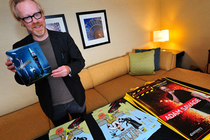Adam Savage, flanked by the limited-edition posters and bags he autographed, shows off the custom MythBusters iPad that was rewarded to the fan who guessed his identity on the Comic Con floor.