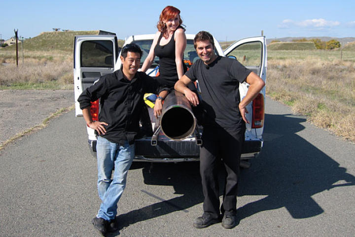 Grant, Tory and Kari posed with the ball-chucker they built to test whether an object fired backward from a vehicle moving forward will simply fall straight to the ground. Can you guess the year? (No need -- it was 2010.)